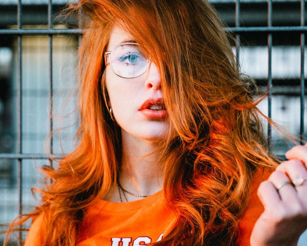 selective focus photo of woman wearing eyeglasses with orange hair