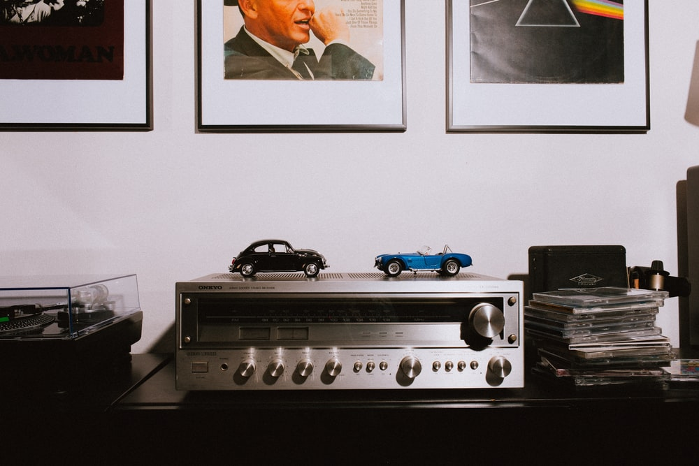 gray AV receiver on brown wooden table
