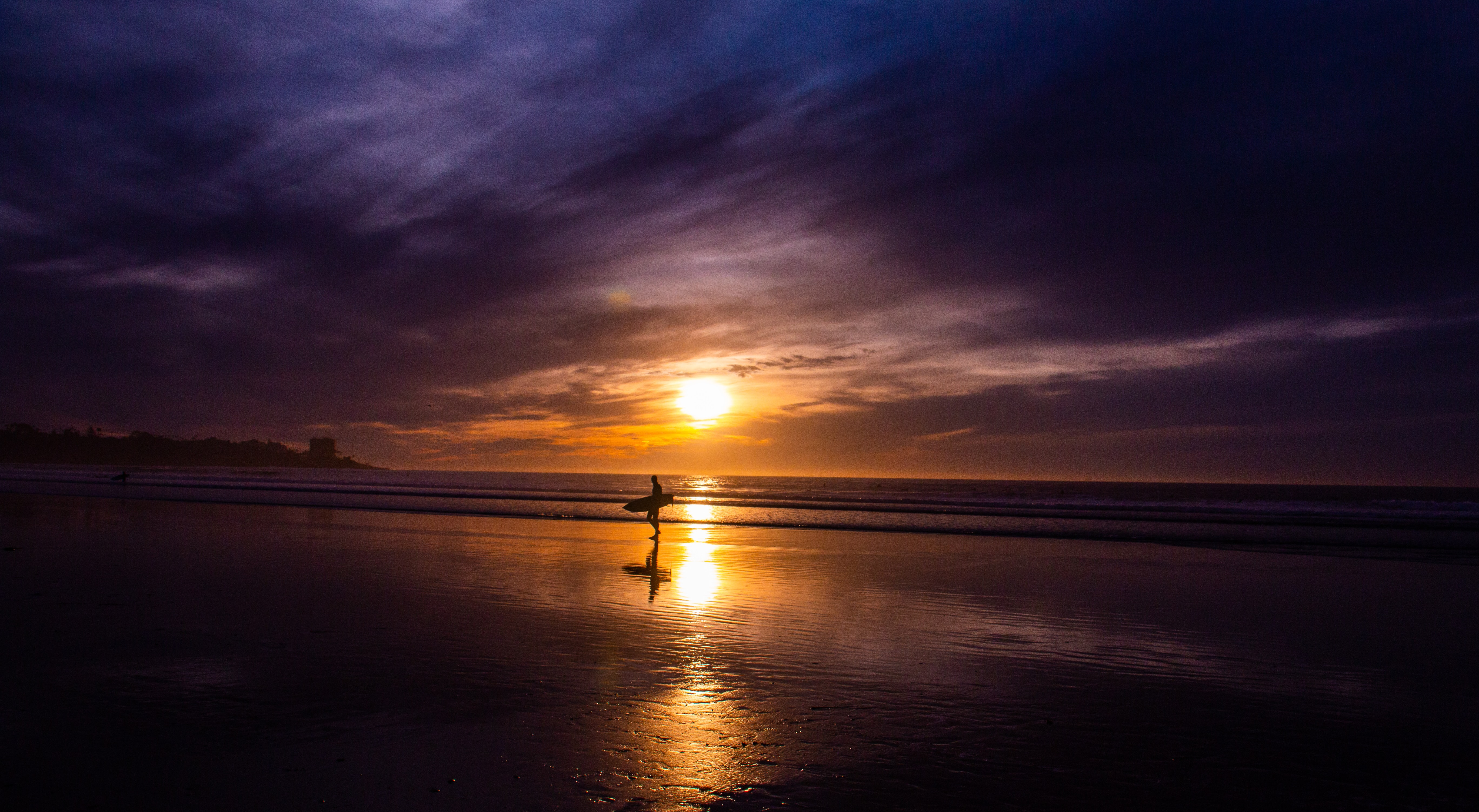 silhouette photography of person standing on shore while holding surfboard