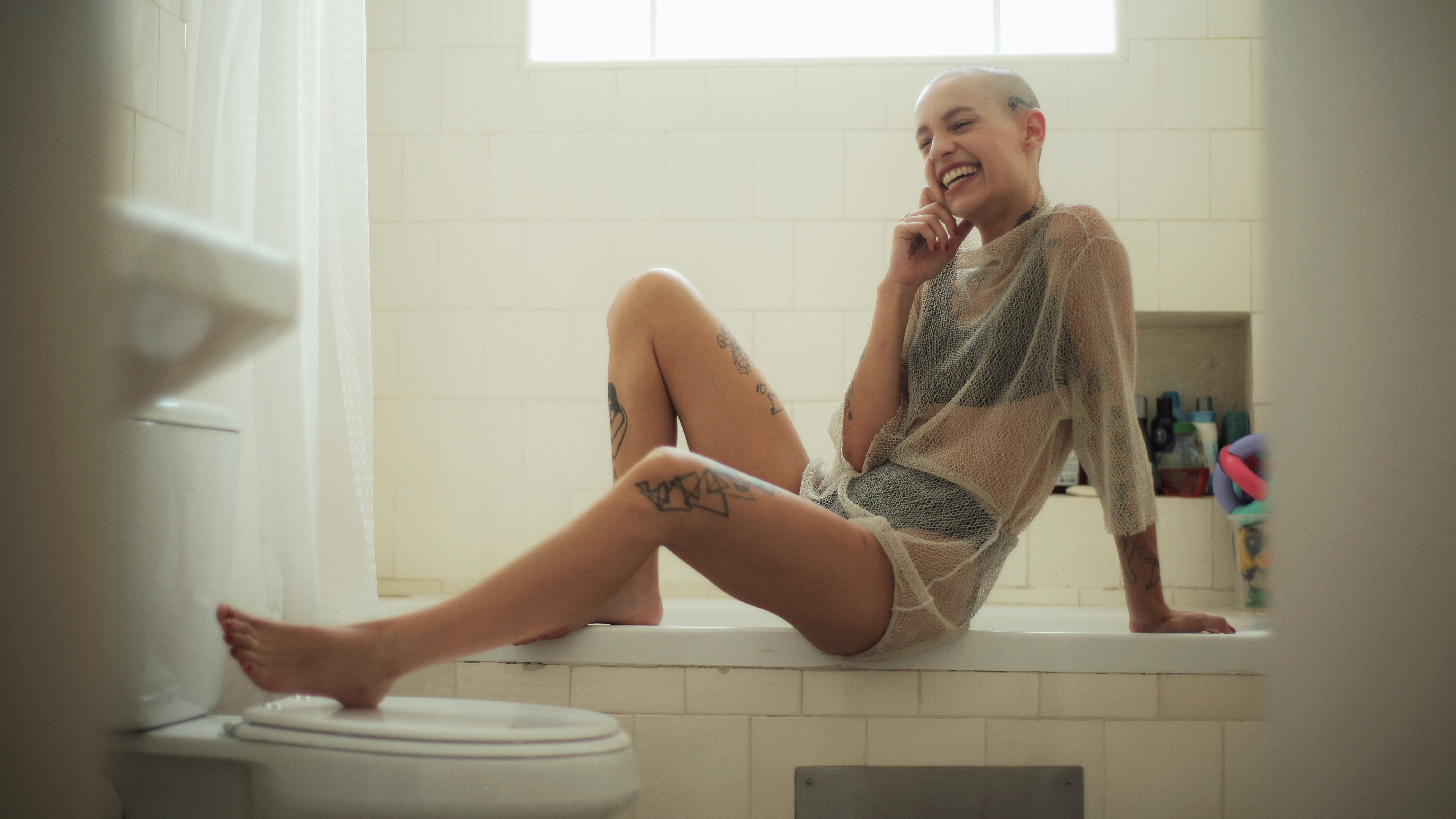 woman in mesh dress sitting on tub smiling during day time
