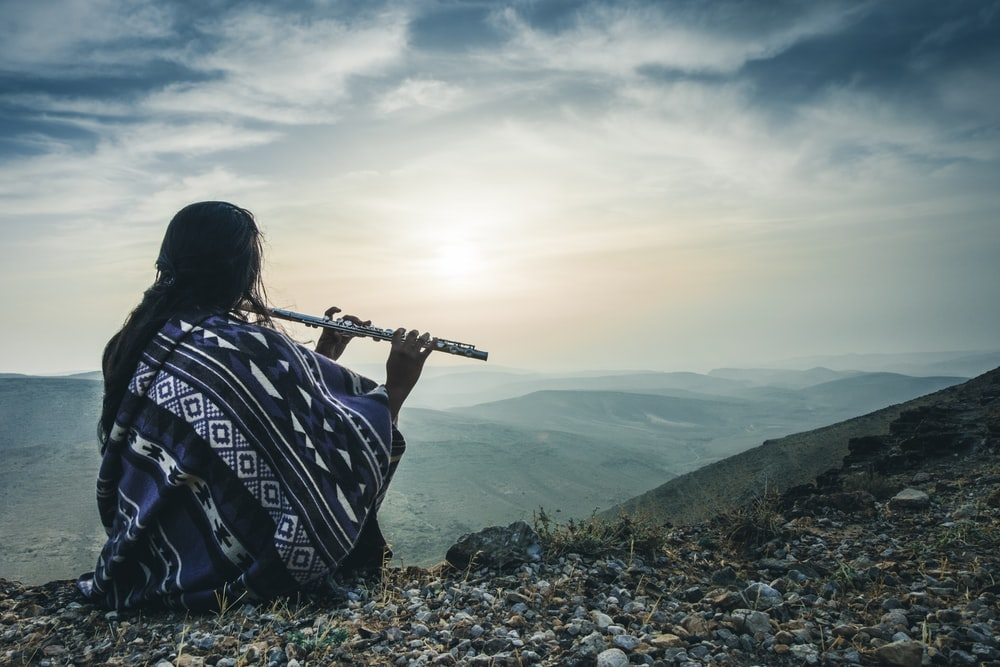 woman playing flute on hill