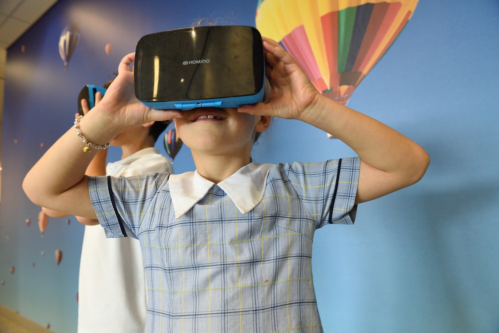 boys using blue and black virtual reality headset