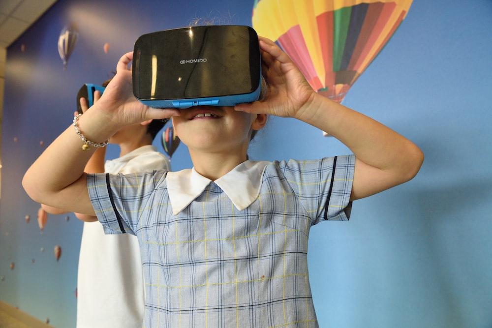 boys using blue and black virtual reality headset