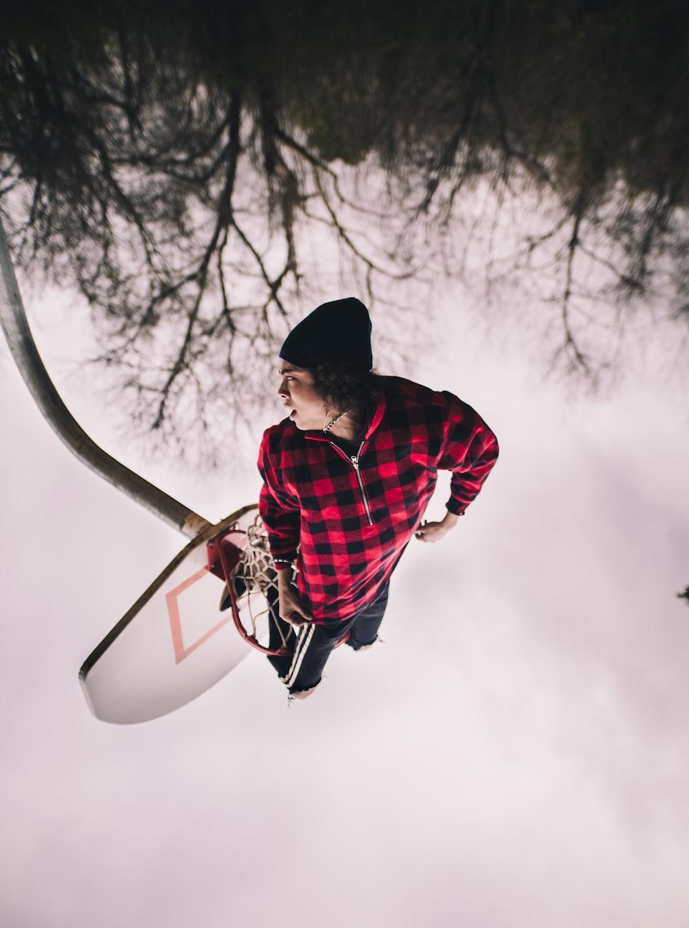 man performing stunt on basketball hoop