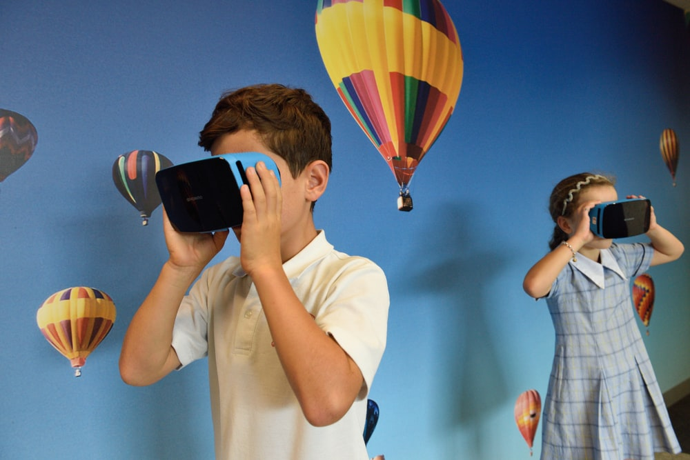 boy and girl uses VR goggles in front hot air balloons wallpaper