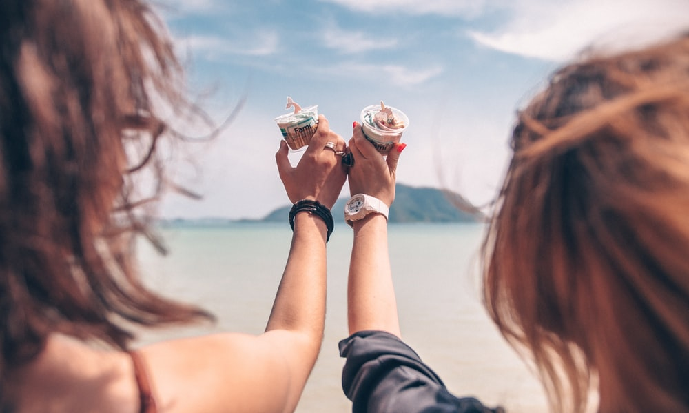 two women holding cup with cream