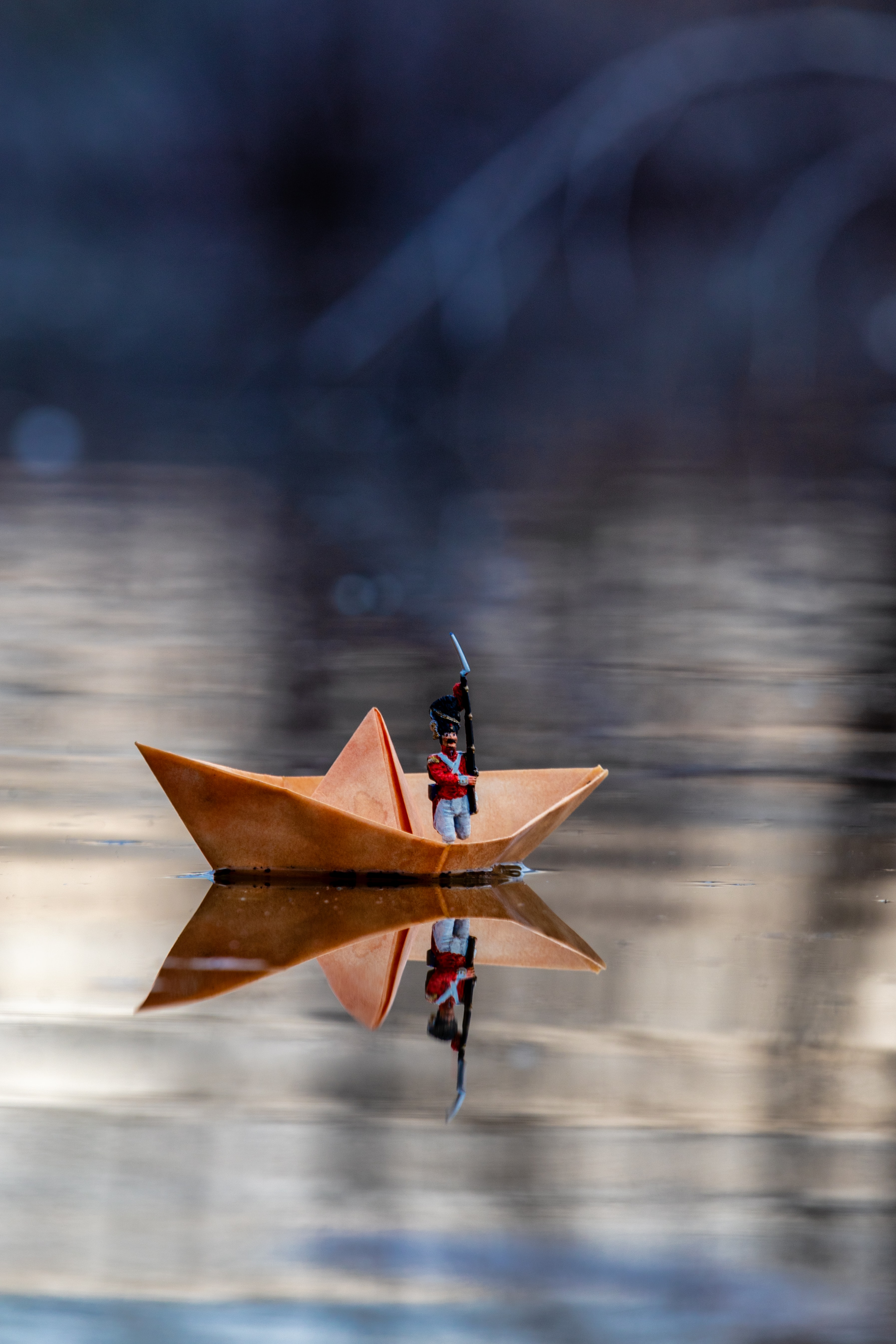 selective focus photography of toy in paper boat on water