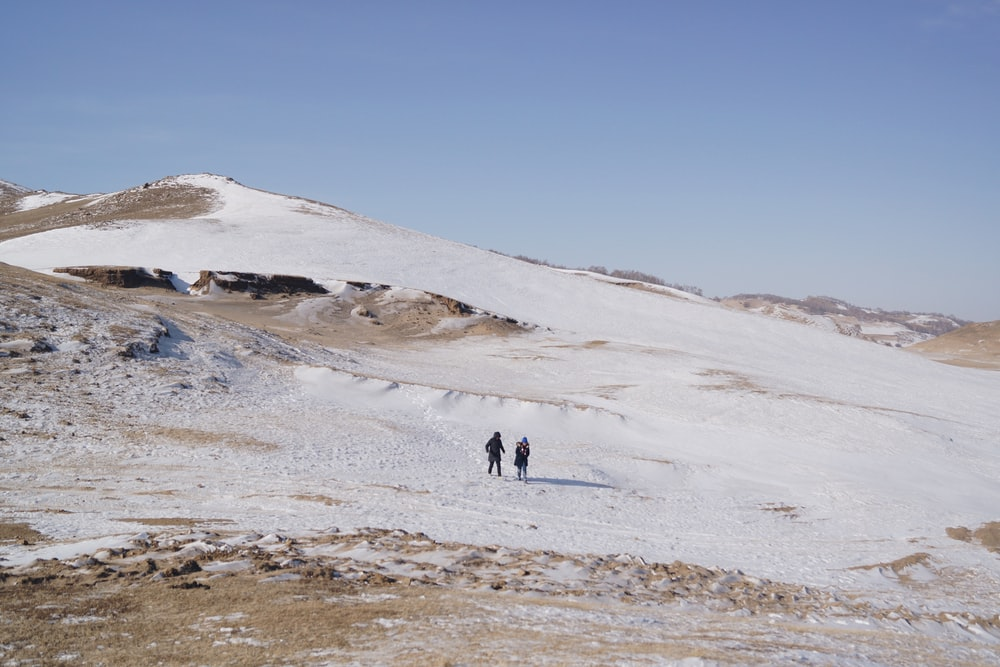 two persons walking on mountain