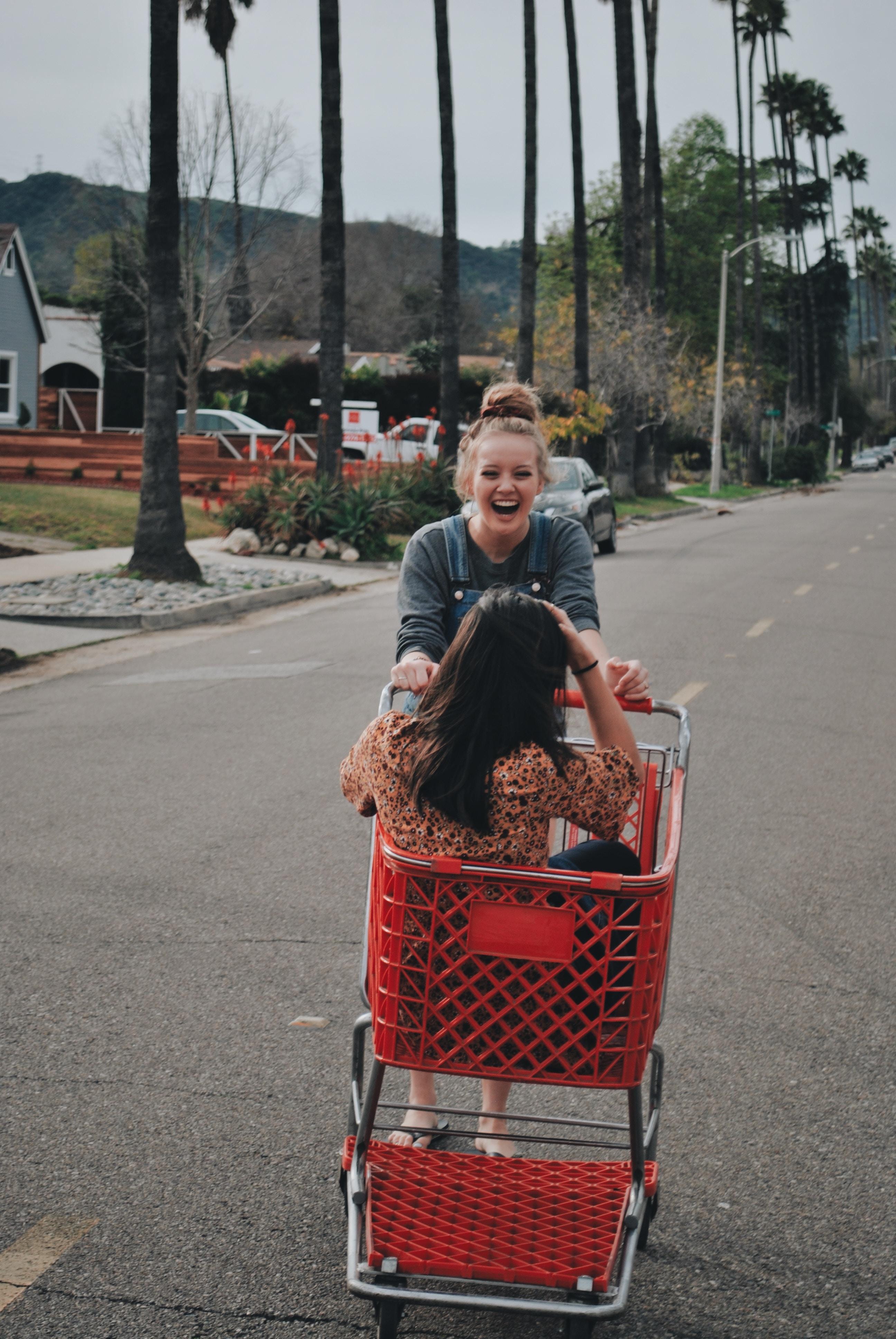 woman pushing shopping cart with woman riding in it