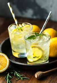 sliced lime in clear drinking glasses with full of clear liquids