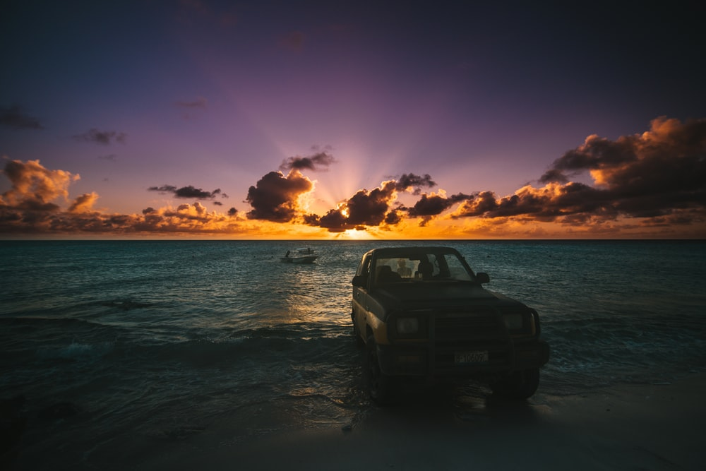 08eee28600 vehicle on seashore during sunset
