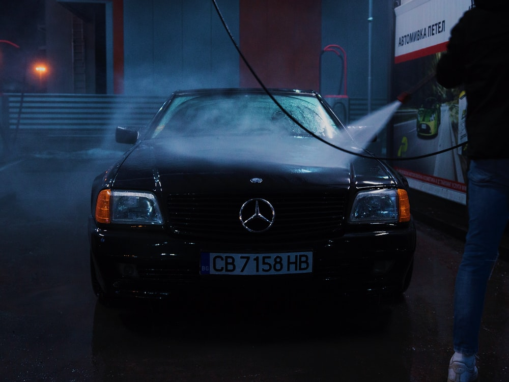 person spraying Mercedes-Benz vehicle with water