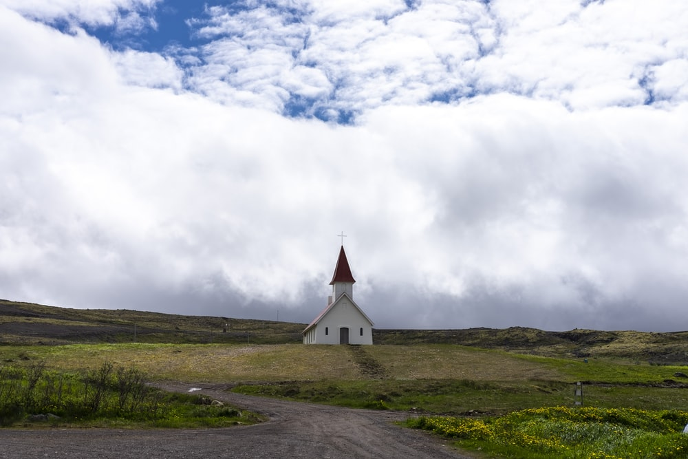 church on green grass under cloudy sky