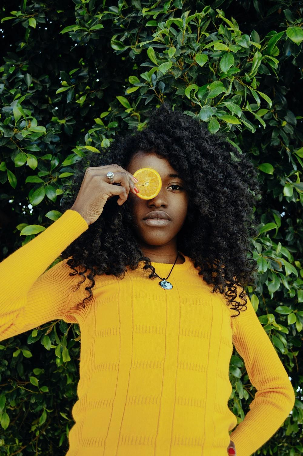woman holding sliced lemon fruit