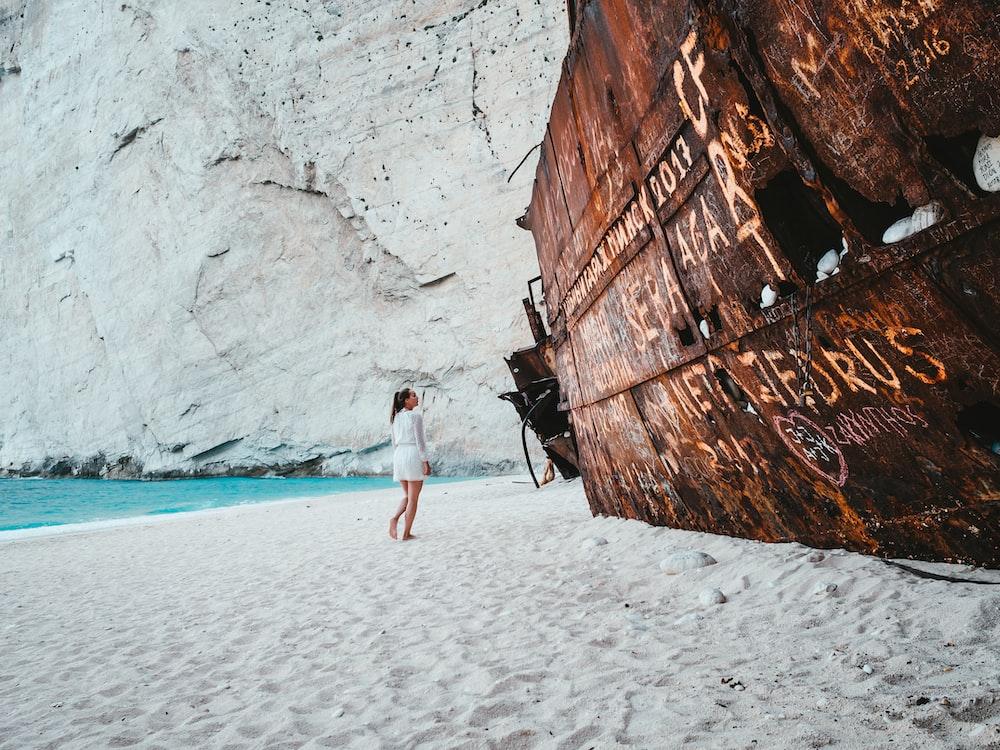 woman standing near brown metal frame on seashore
