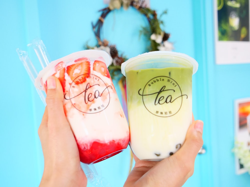 person holding two assorted-flavored milk tea cups