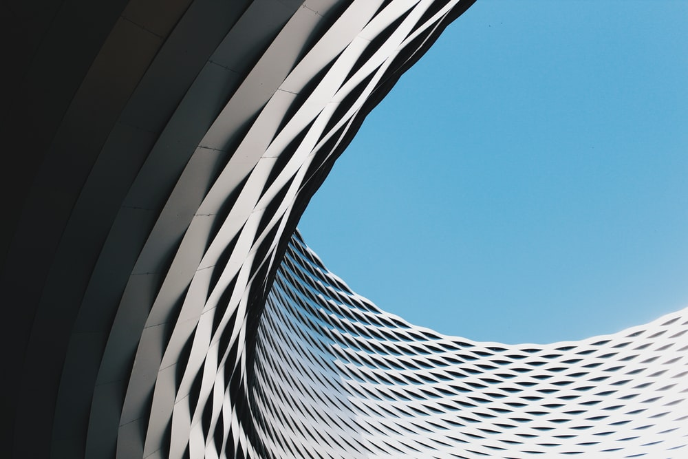 grey curved concrete structure under blue sky during daytime