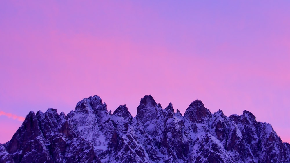 pink sky over snow rocky mountains