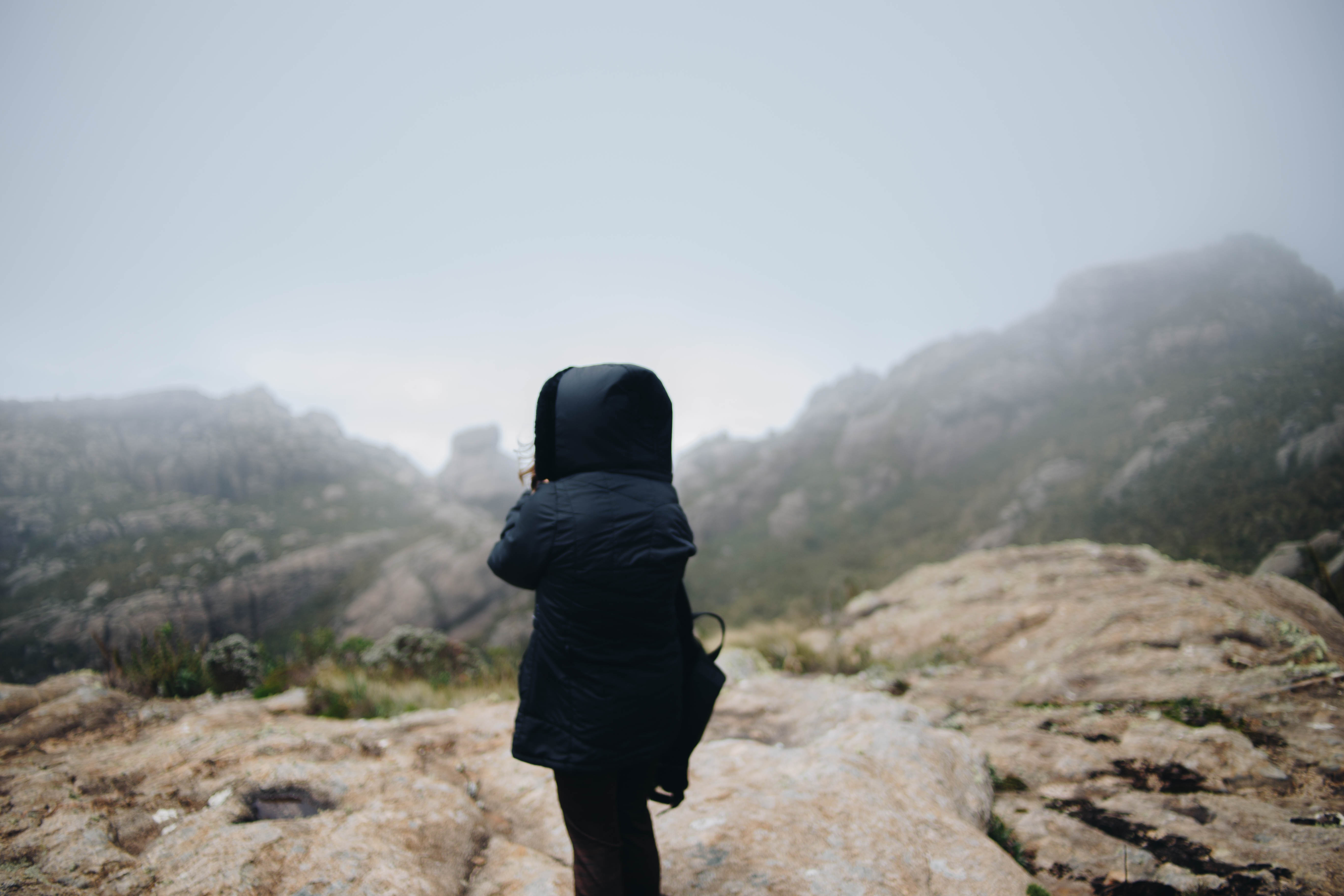 person wearing black hoodie bubble jacket standing on mountain