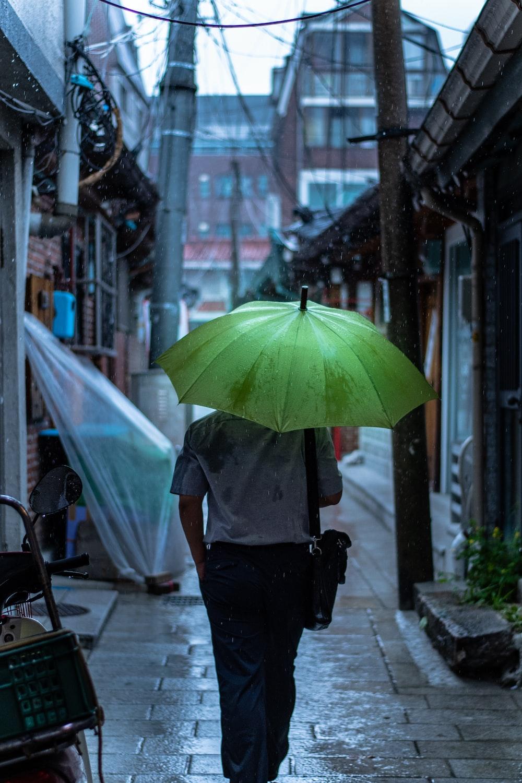 person walking while raining during daytime