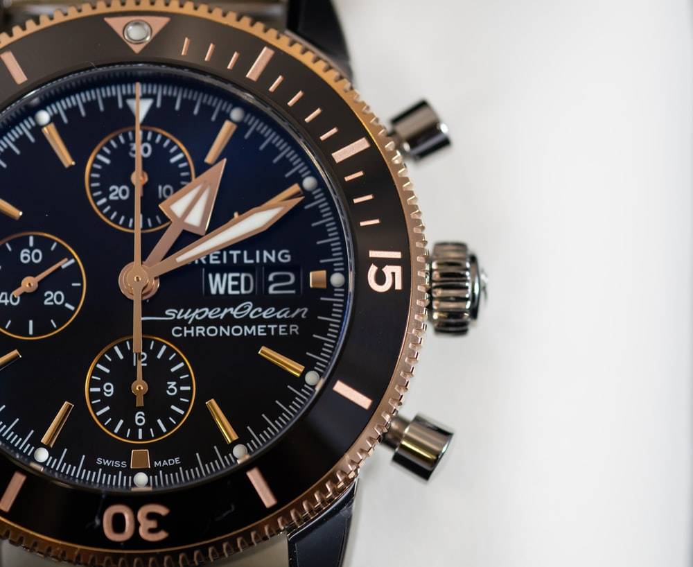 round black and gold-colored Brietling chronograph watch