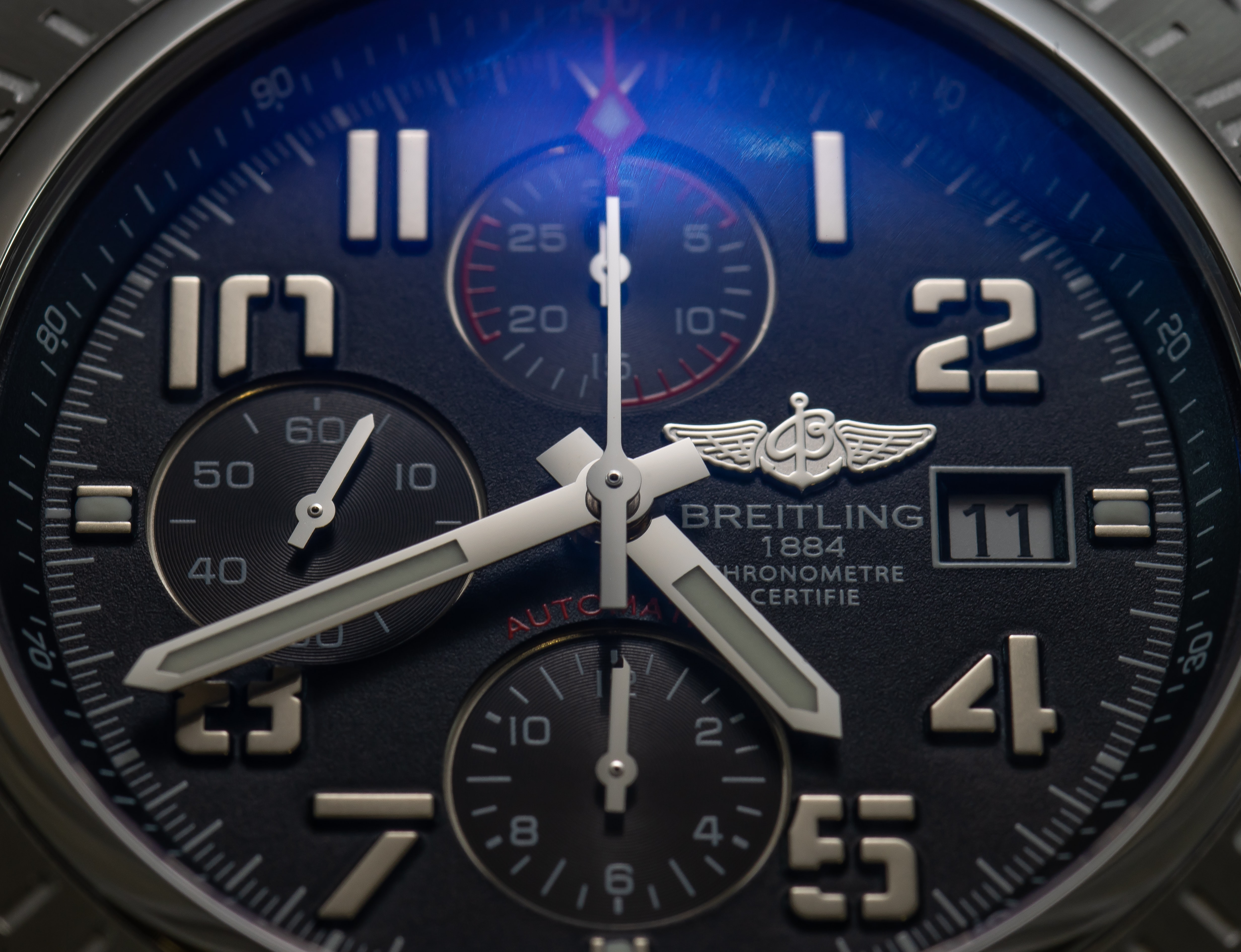 round gray and black Breitling chronograph watch at 4:42