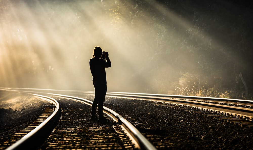 person holding camera standing on train track while taking photo