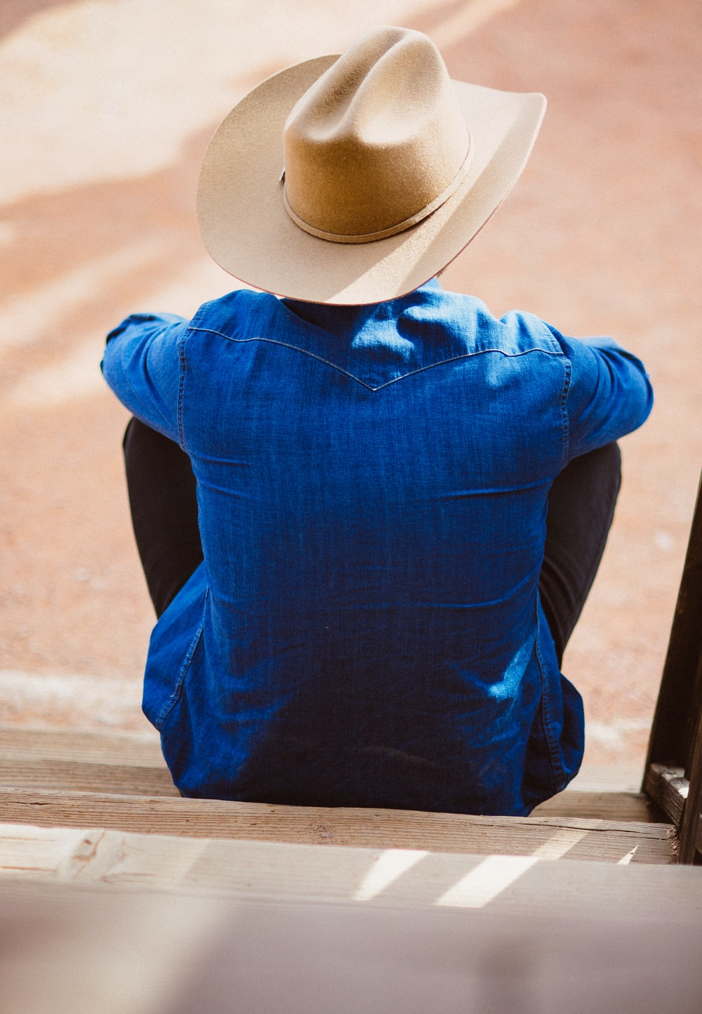 man wearing blue dress shirt and beige cowboy hat