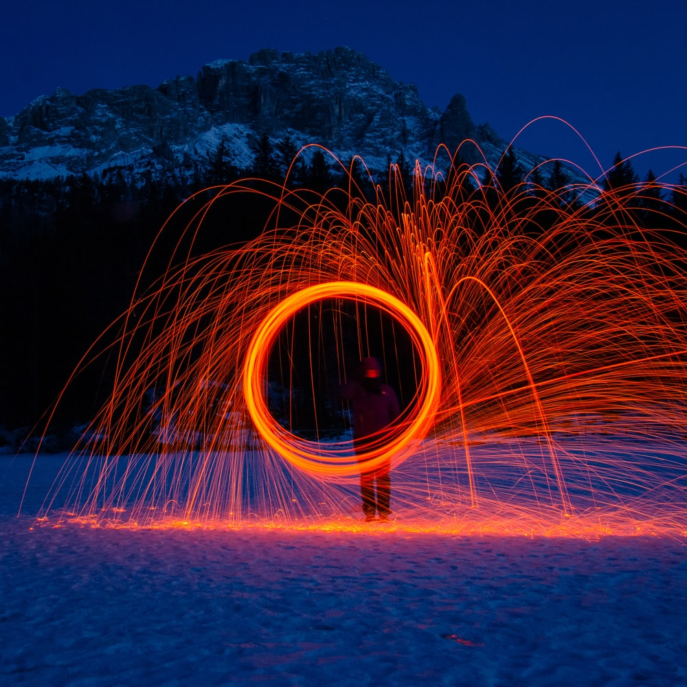 person holding red fire sparks