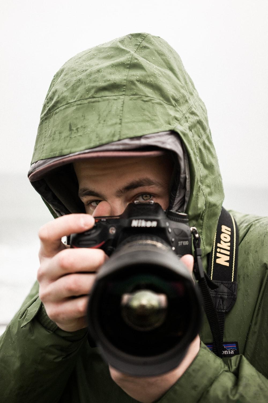 man holding Nikon DSLR camera