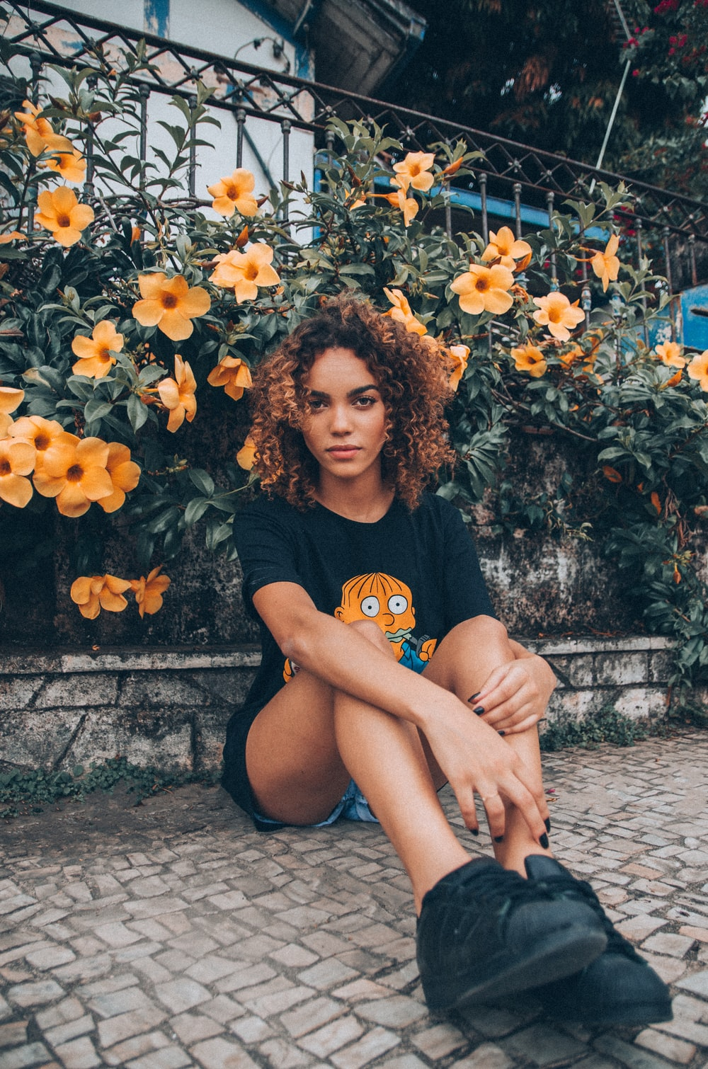 girl sitting on floor with flower behind during daytime