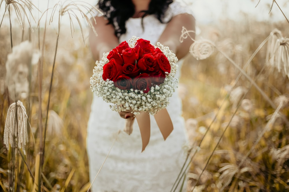 woman holding red flowers bouquet