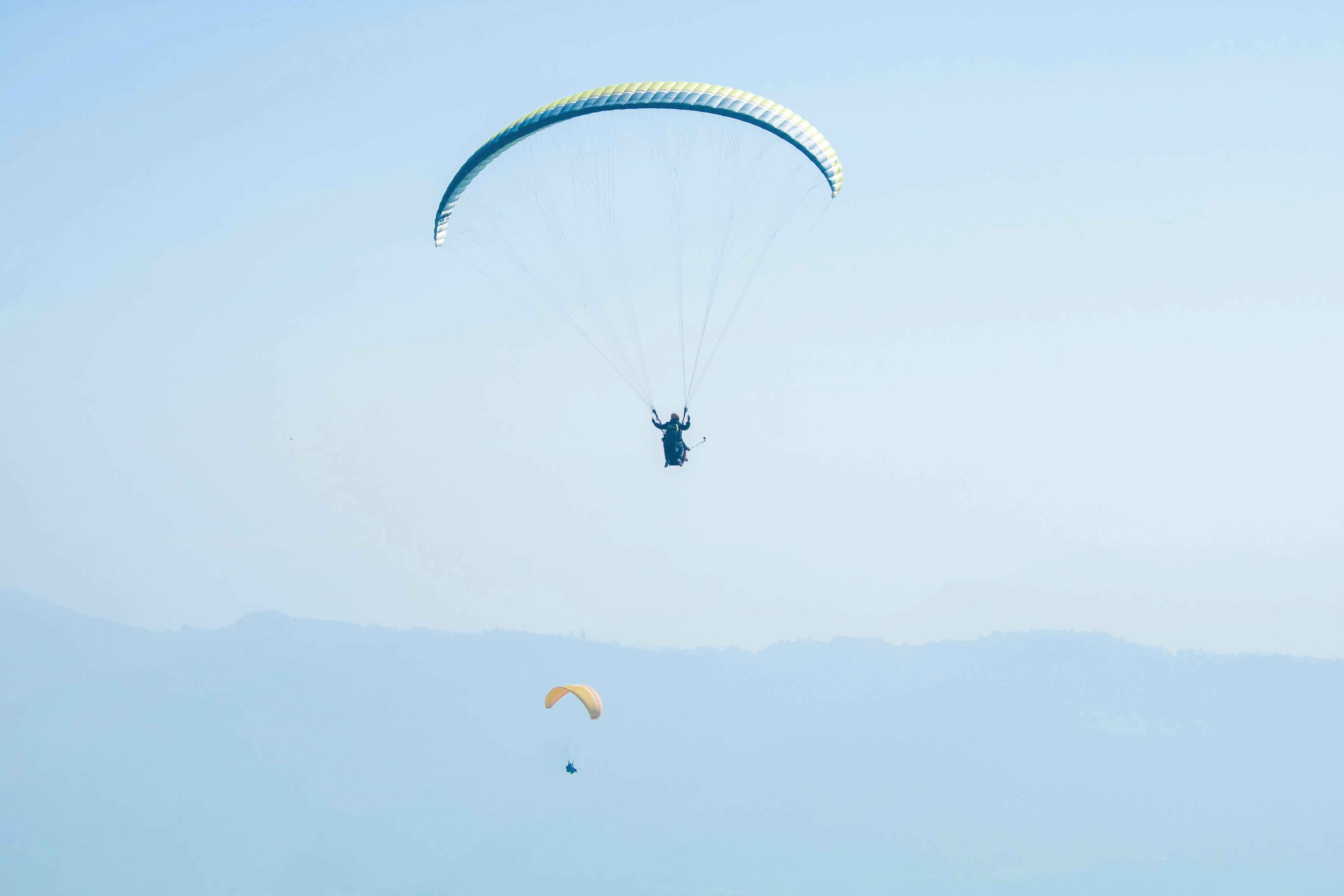 man parachuting under blue sky
