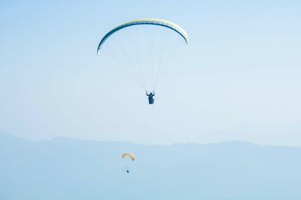 man parachuting under blue sky