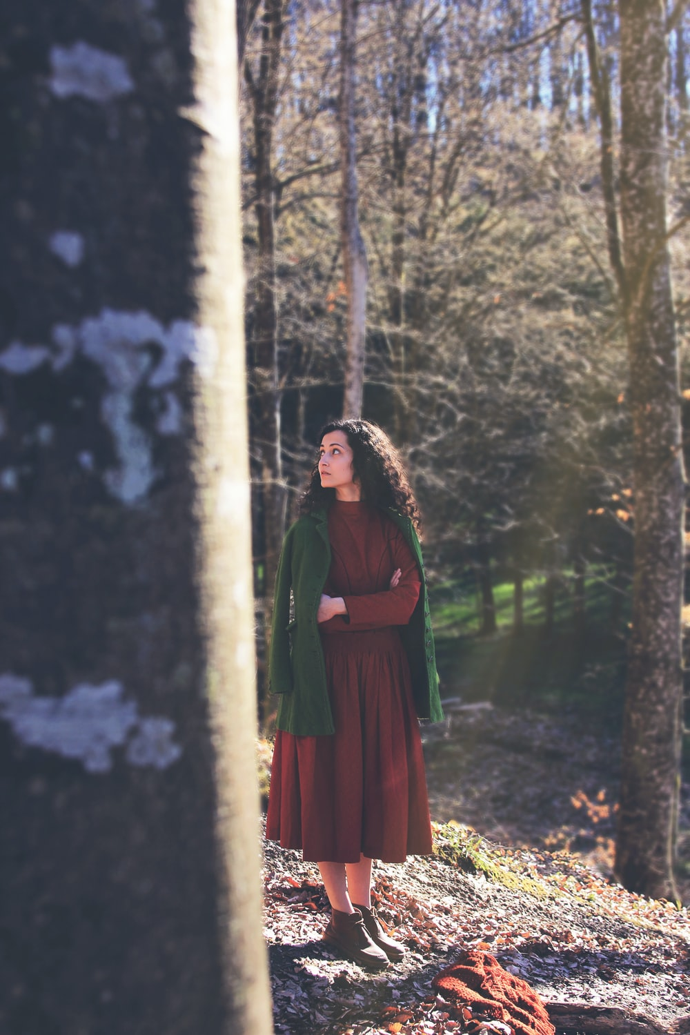 woman wearing red long sleeved dress walking in middle of woods