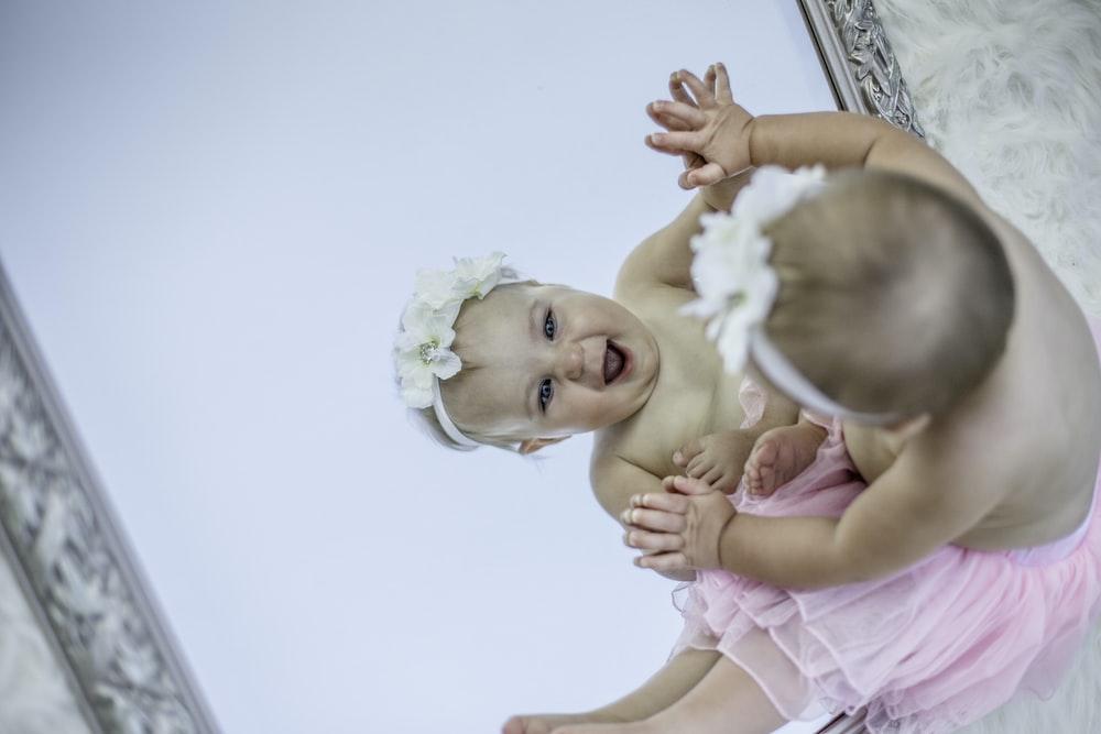 toddler facing mirror while smiling