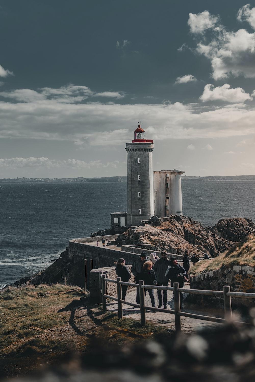 people walking towards gray lighthouse