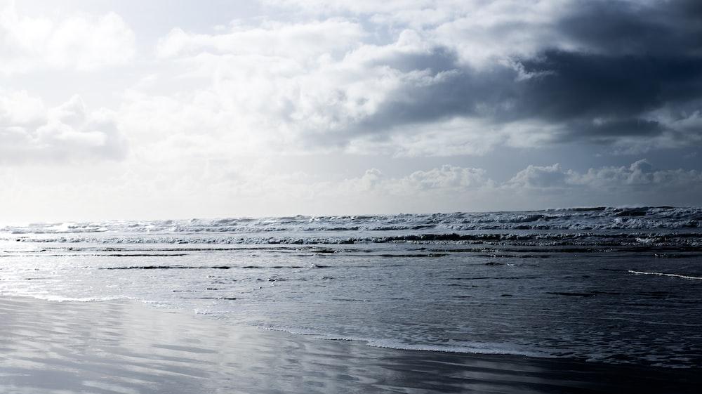 calm sea under cloudy sky