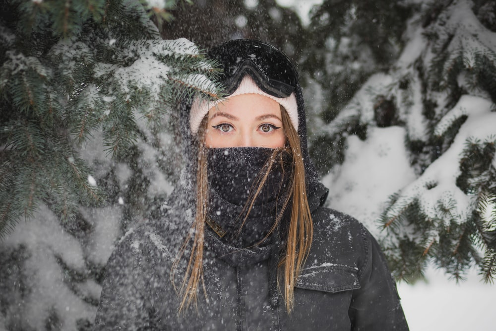 woman with mask standing beside pine tree covered with snow