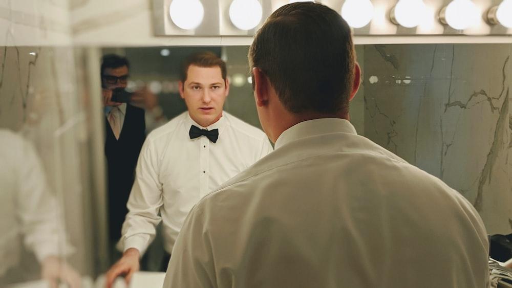 man wearing white dress shirt and black bowtie facing vanity mirror