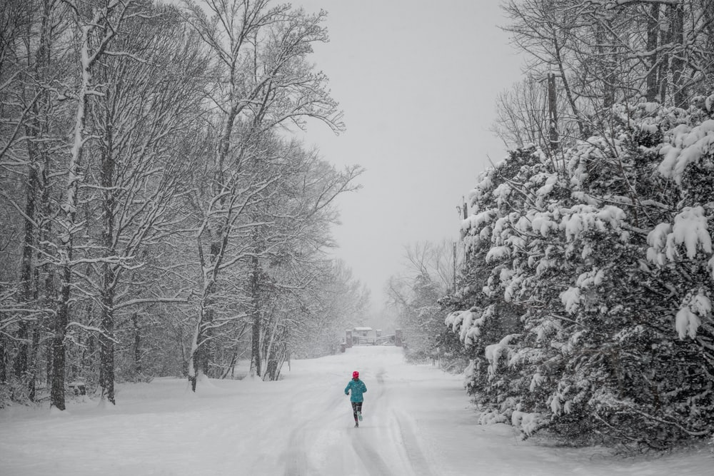 person jogging on snow capped pathway