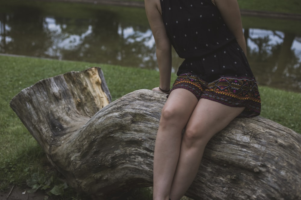 woman sitting on wood log near body of water