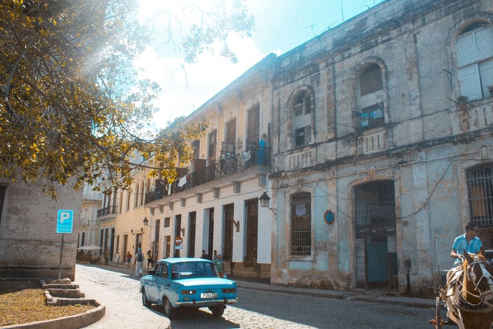 blue sedan passing on road beside building