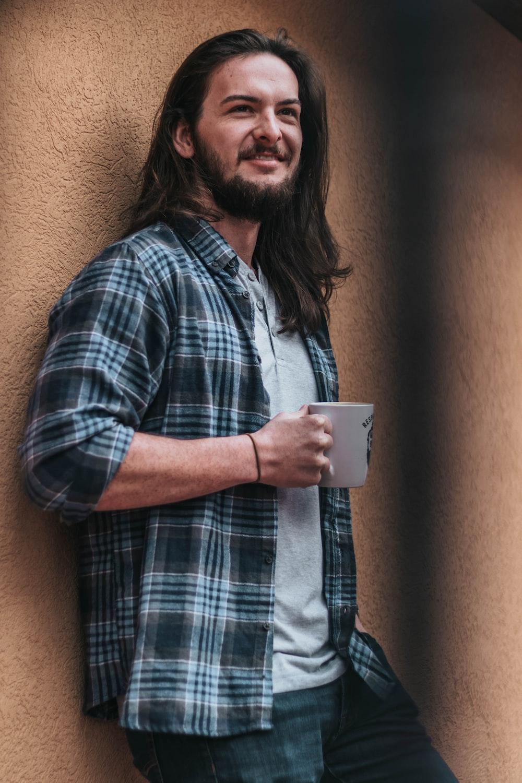 man holding mug leaning on wall