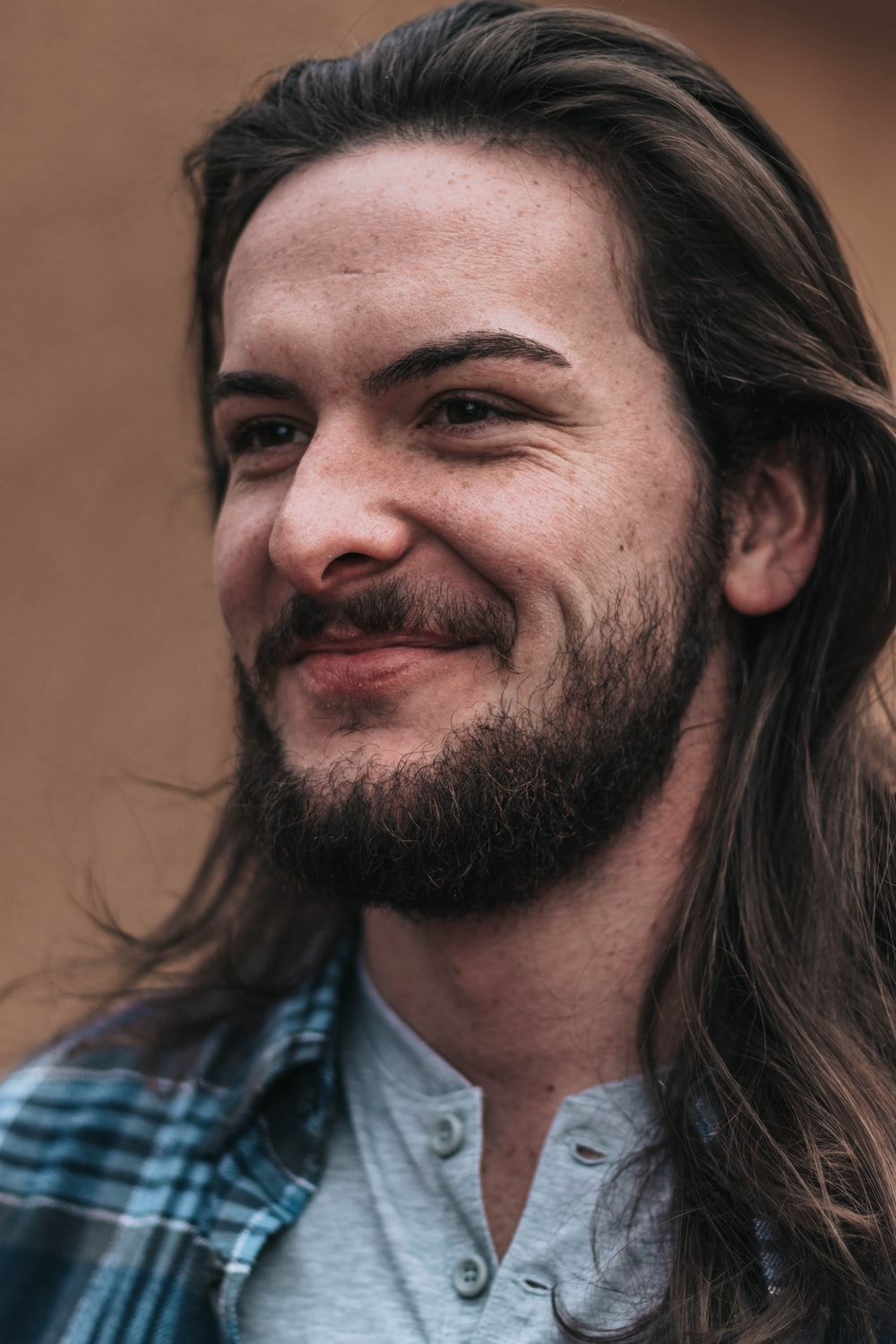smiling man in blue and black plaid shirt