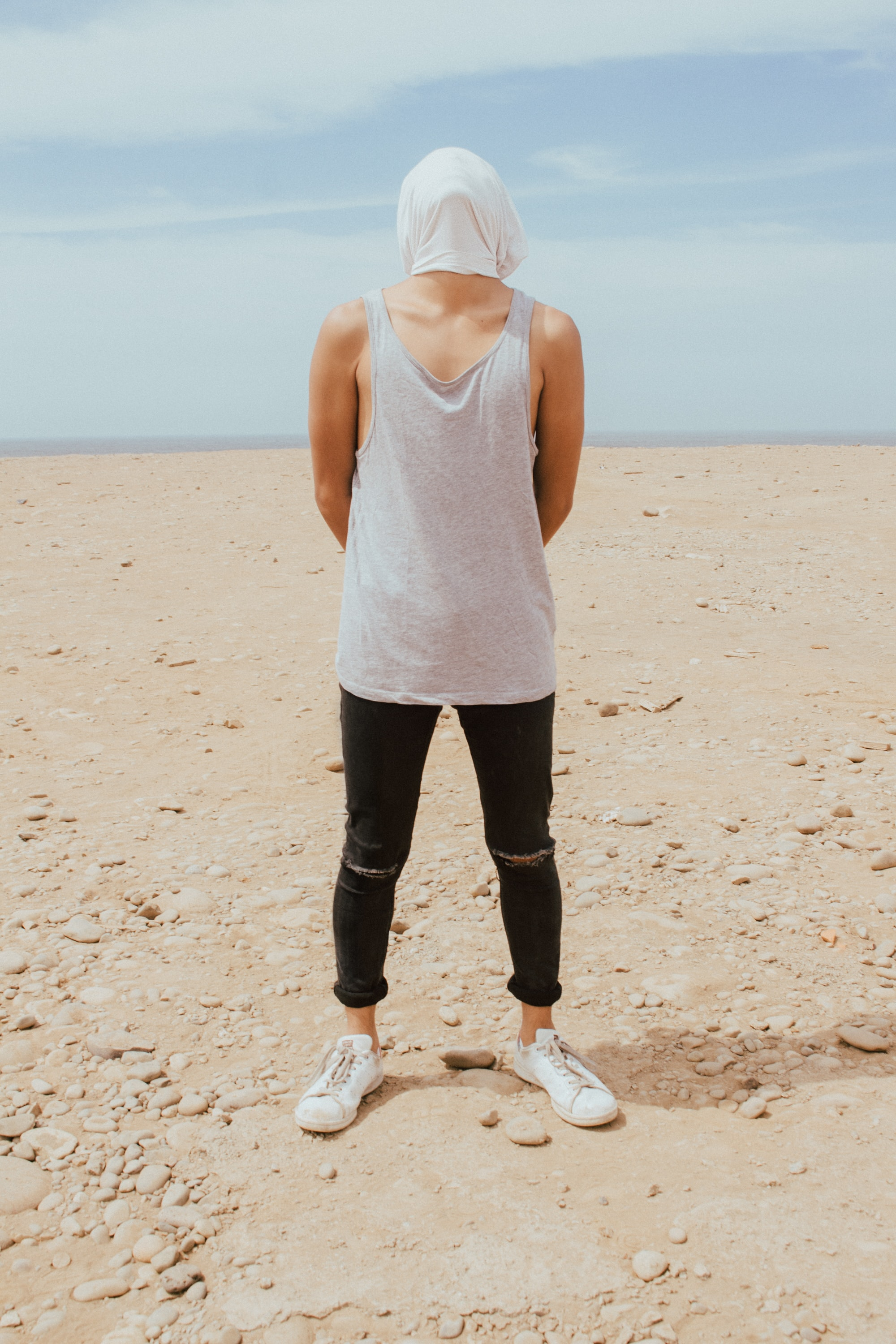 standing man in white tank top covering his face with white textile