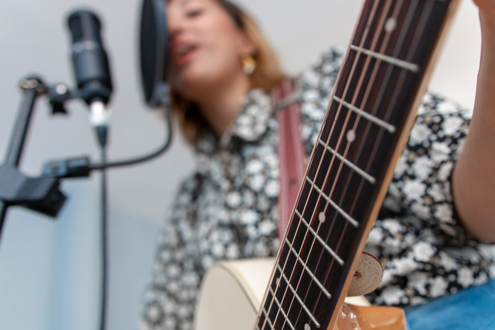 woman playing acoustic guitar while singing using condenser microphone