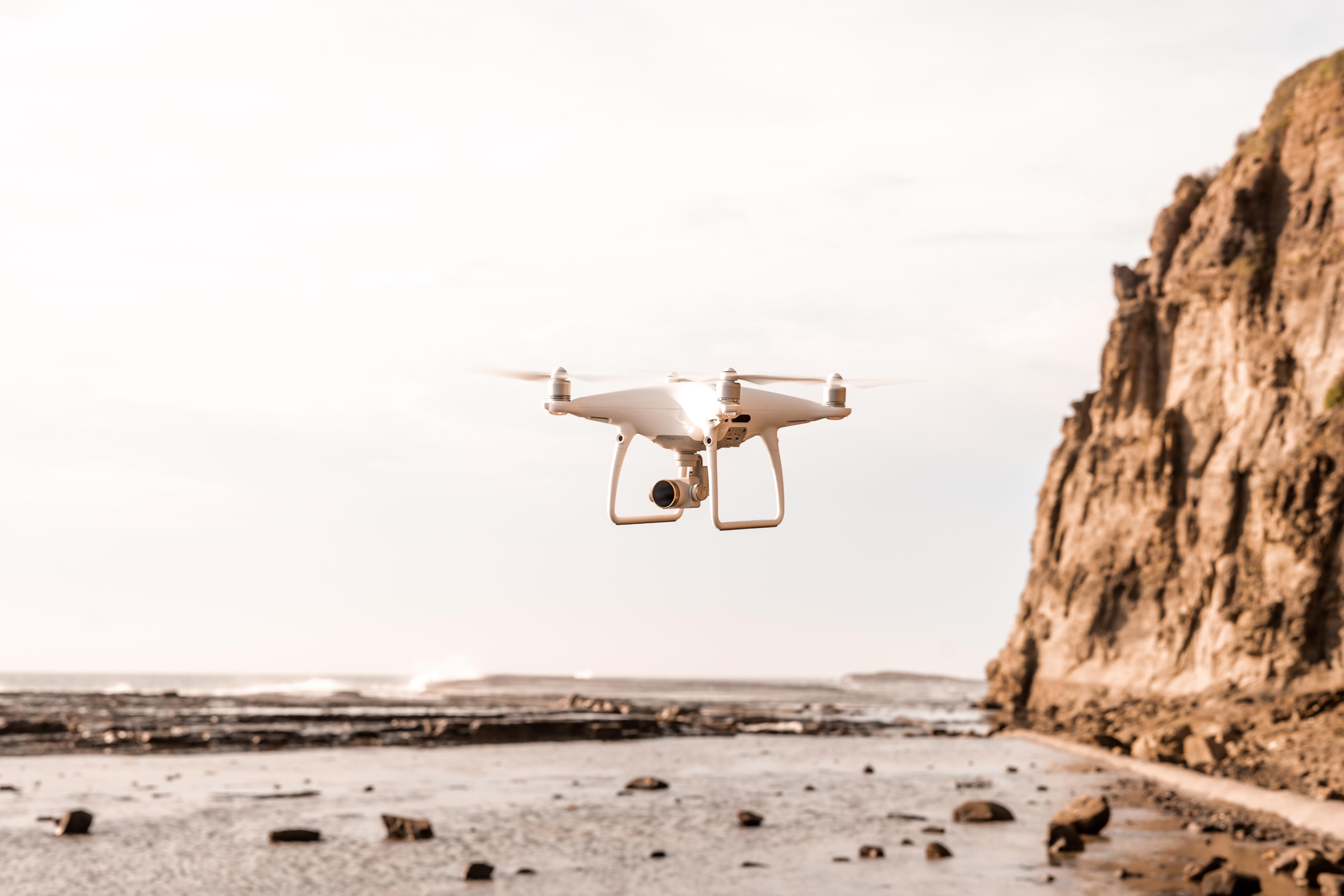 white drone near seashore
