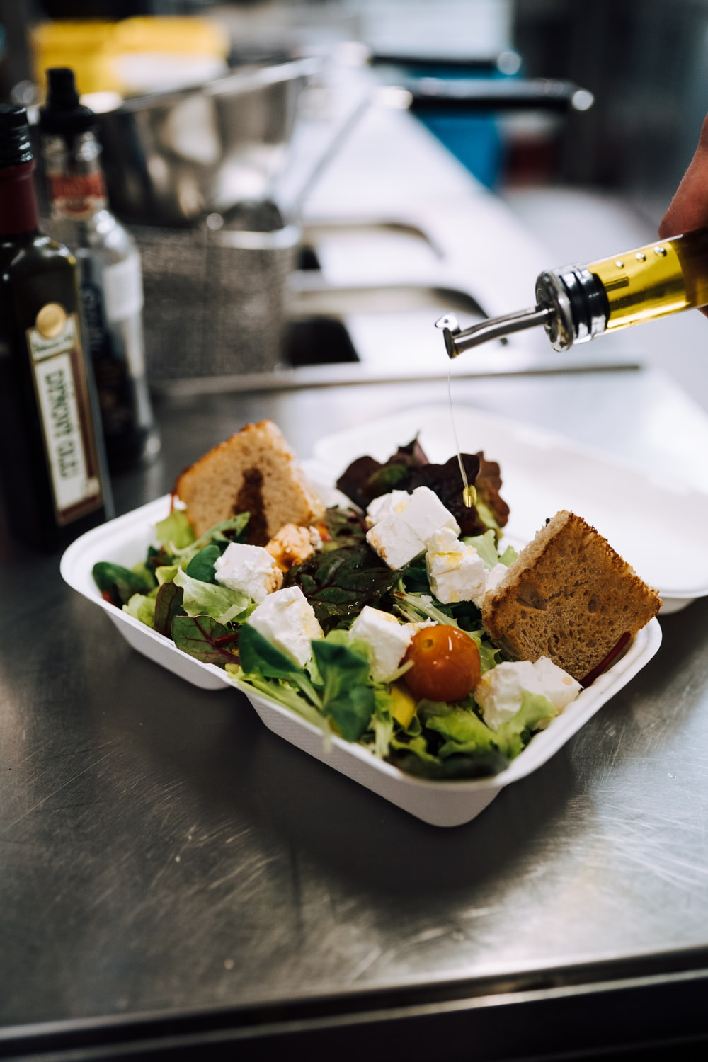 olive oil poured into green vegetable salad with cheese and croutons