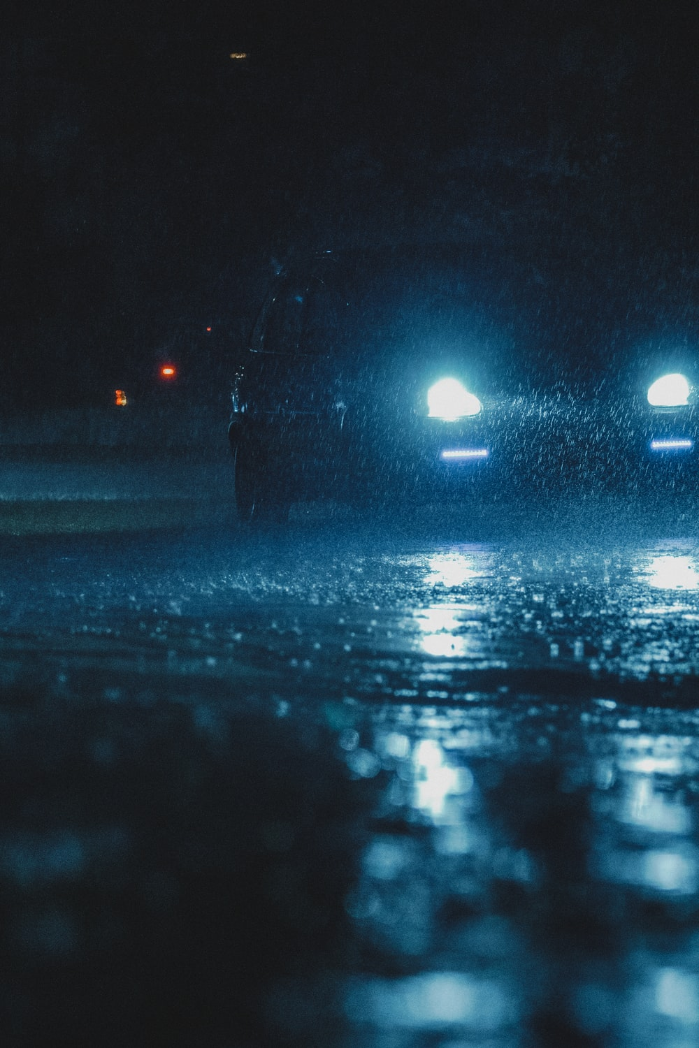 vehicle with headlight turned on running on wet road during nighttime